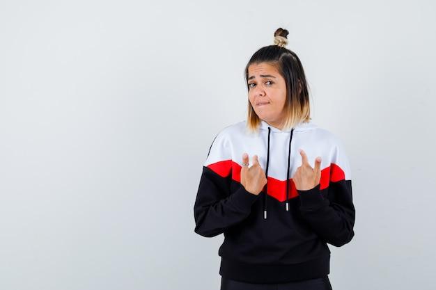 Jeune femme se pointant sur elle-même comme posant une question dans un pull à capuche et semblant prudente.