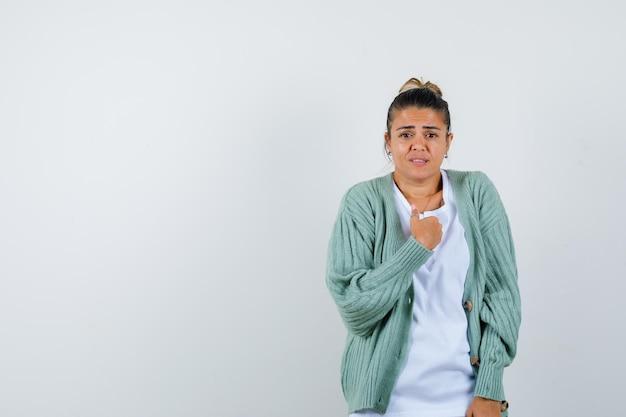 Jeune femme se pointant en t-shirt, veste et l'air fière