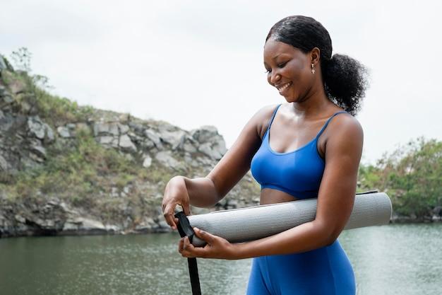 Jeune femme se préparant à un cours de yoga en ligne