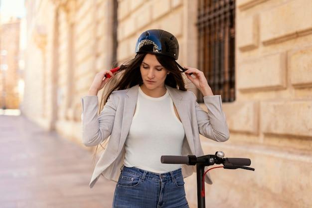 Jeune femme se préparant à monter dans un scooter électrique dans la ville