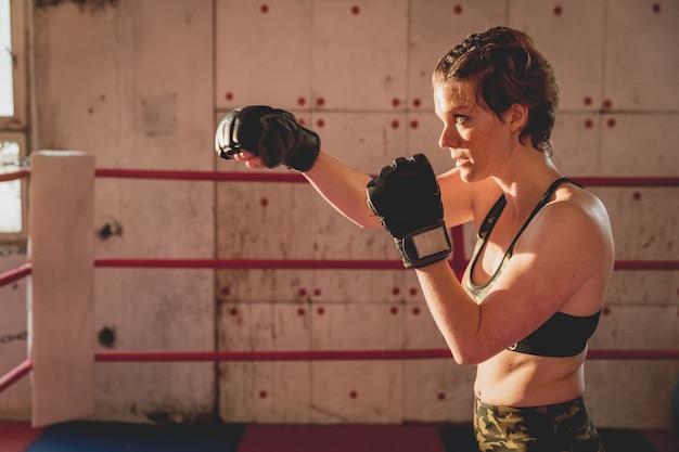 Jeune femme se prépare pour les matchs mma dans la cage. entraînement dans une salle de sport