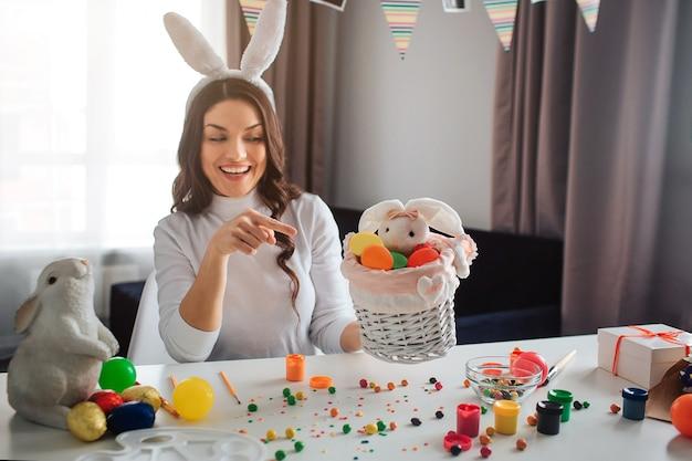 Jeune femme se prépare seule pour pâques. elle est assise à table dans la chambre et tient un panier avec un lapin et des œufs colorés. point de modèle sur elle. elle sourit.