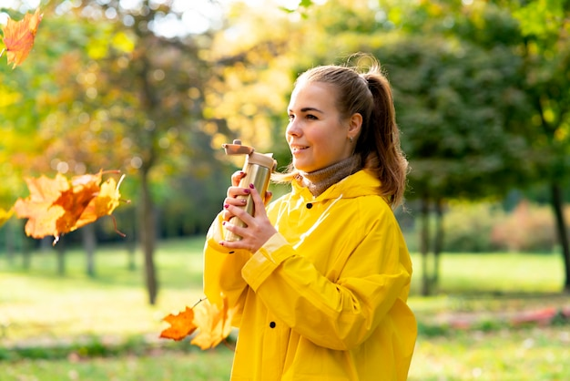 Une jeune femme se promène dans le parc en automne doré, une fille en imperméable boit du thé dans un thermos confort