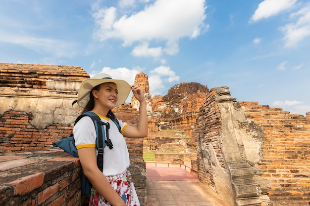 Une jeune femme se promène dans le vieux temple de phra nakhon si ayutthaya, en thaïlande, pendant une journée de détente.