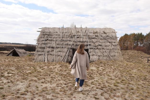 Jeune femme se promène près des vieilles maisons rustiques de paille