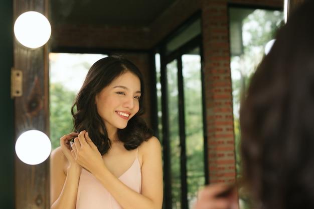 Jeune femme se regardant reflet dans un miroir à la maison