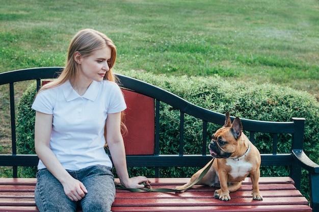 Jeune femme se reposant sur un banc dans le parc avec son chien en été