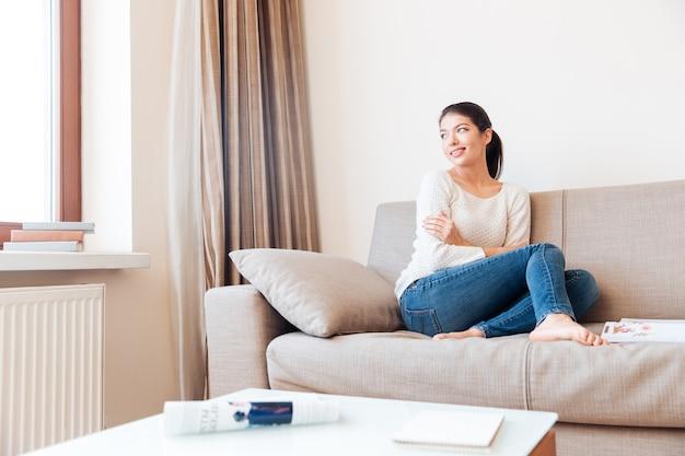 Jeune femme se reposant sur le canapé et regardant la fenêtre