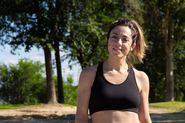 Jeune femme se reposant et souriant à la caméra après avoir pratiqué le sport mode de vie sain