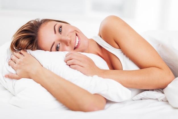 Jeune femme se réveille après avoir dormi sur le linge blanc au lit à la maison