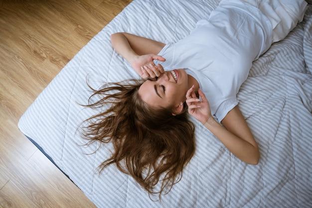 Une jeune femme se réveille après une bonne nuit de sommeil dans son lit sentiments d'excitation femme heureuse en pa...