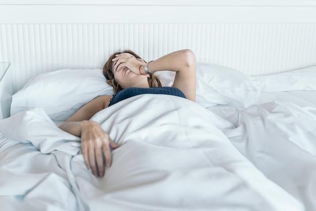 Jeune femme se réveille dans son lit avec un mal de tête et peu envie de commencer la journée.