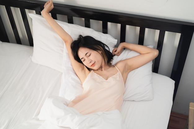 Jeune femme se réveille sur le lit dans la chambre à la maison