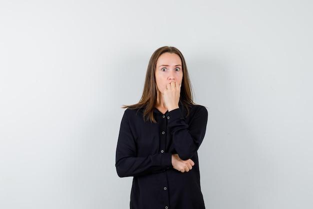 Jeune femme se rongeant les ongles et semblant anxieuse