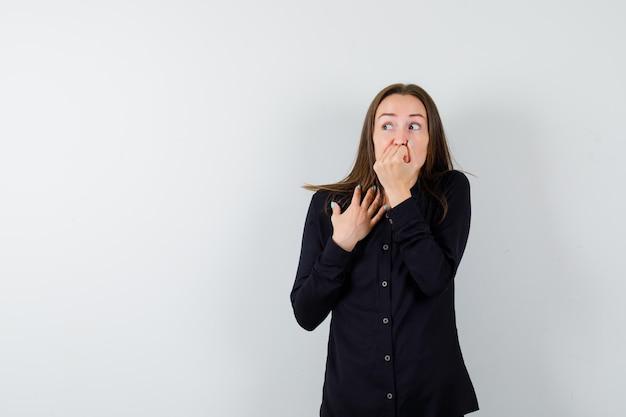Jeune femme se ronger les ongles et avoir l'air effrayée