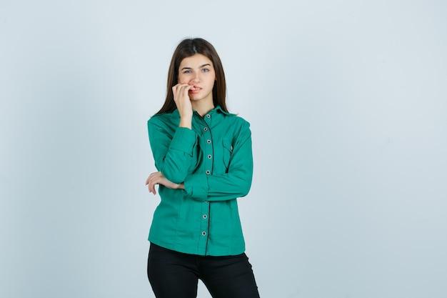 Jeune femme se ronger les ongles en chemise verte, pantalon et à la troublée. vue de face.