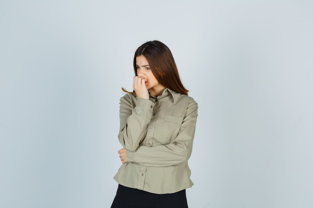 Jeune femme se ronger les ongles avec émotion en chemise, jupe et semblant anxieuse. vue de face.