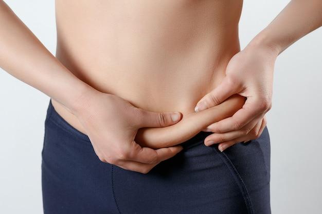 Une jeune femme se sent avec deux mains repliées sur le ventre.