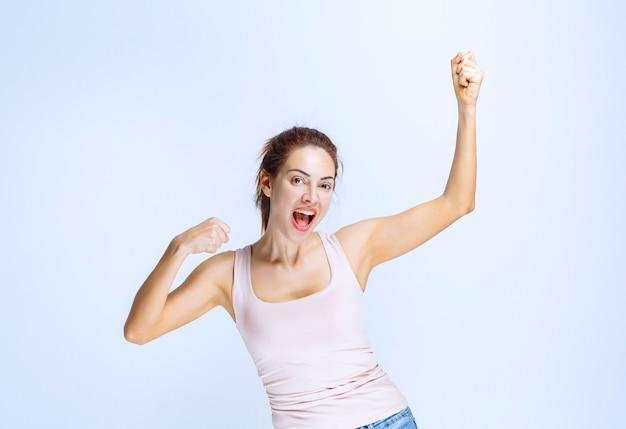 La jeune femme se sent heureuse et montre des signes positifs de la main
