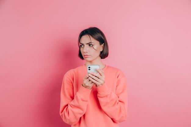 Jeune femme se sent triste malheureuse en colère lors de la lecture de sms à l'aide de son téléphone portable, sur fond rose