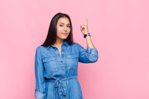 Jeune femme se sentant comme un génie tenant le doigt fièrement en l'air après avoir réalisé une excellente idée, disant eureka