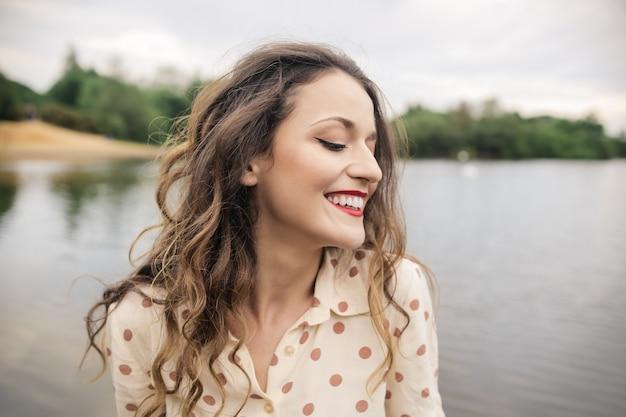 Jeune femme se sentant détendue près du lac