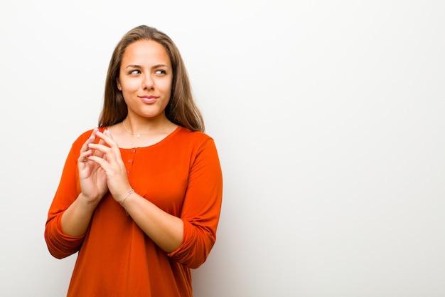 Jeune femme se sentant fière, espiègle et arrogante tout en préparant un plan diabolique ou en pensant à un truc
