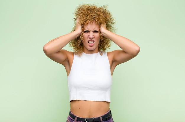 Jeune femme se sentant frustrée et ennuyée, malade et fatiguée de l'échec, marre des tâches ennuyeuses et ennuyeuses sur le mur vert