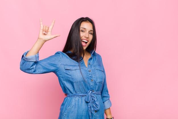 Jeune femme se sentant heureuse, amusante, confiante, positive et rebelle, faisant du rock ou du heavy metal signe avec la main