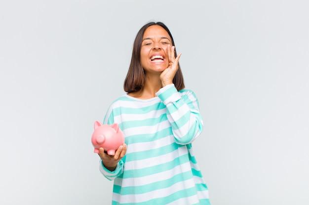 Jeune femme se sentant heureuse, excitée et positive, donnant un grand cri avec les mains à côté de la bouche, appelant