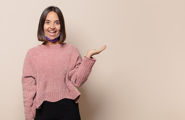 Jeune femme se sentant heureuse, surprise et joyeuse, souriante avec une attitude positive, réalisant une solution ou une idée