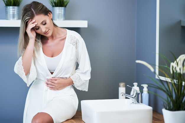 Jeune femme se sentant mal dans la salle de bain