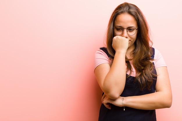 Jeune femme se sentant sérieuse, réfléchie et inquiète, regardant de côté avec la main pressée contre le menton sur fond rose