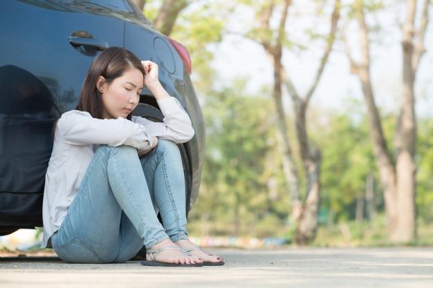 Jeune femme se sentir triste à cause de sa voiture en panne