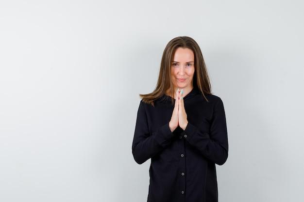 Jeune femme se tenant la main dans un geste de prière