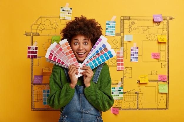Jeune femme se tient à côté de l'esquisse de conception de maison prête pour la rénovation