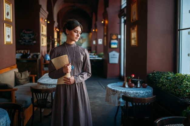 Jeune femme se tient à l'intérieur du café