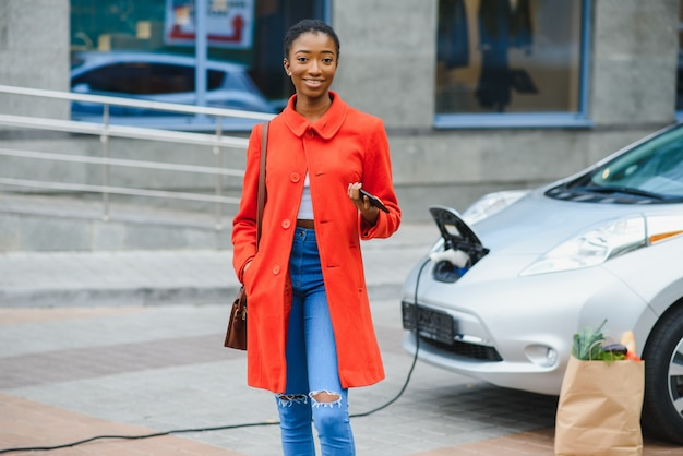 Jeune femme se tient près de la voiture électrique et regarde la caméra