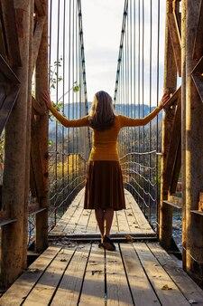 Une jeune femme se tient avec son dos à l'ancien pont suspendu