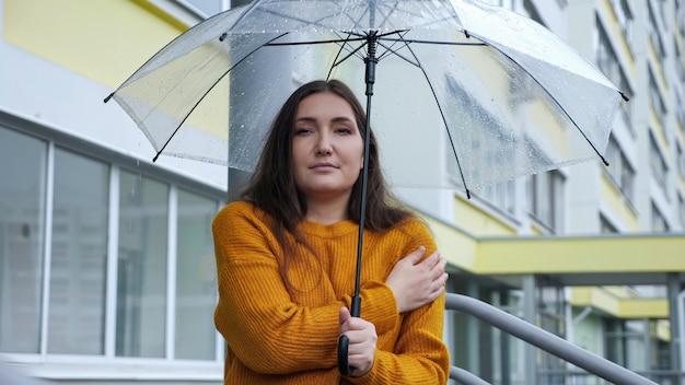 Jeune femme se tient sous un parapluie transparent sous la pluie par temps froid, ralenti
