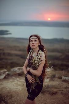 Jeune femme se trouve dans la nature dans une robe noire
