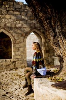 Jeune femme, séance banc, regarder, jaune, feuilles, arbre, automne, parc