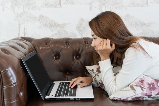 Jeune, femme, séance, divan, utilisation, ordinateur