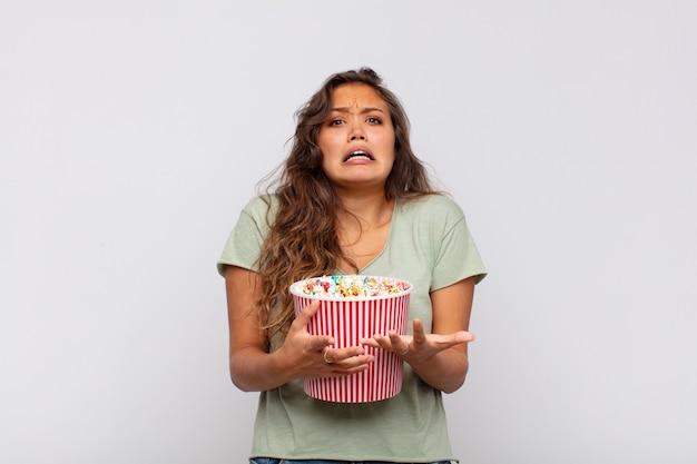 Jeune femme avec un seau pop conrs à la recherche désespérée et frustrée, stressée, malheureuse et agacée, criant et hurlant