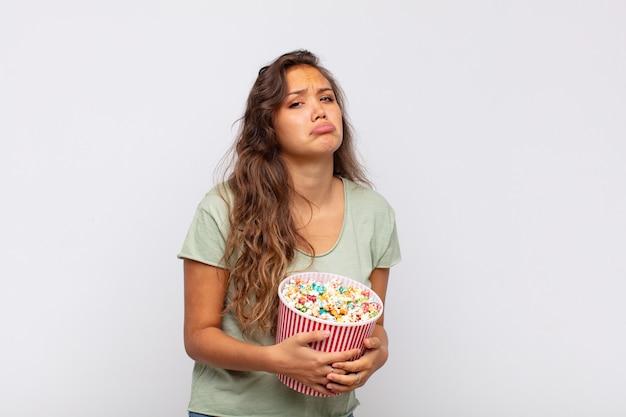 Jeune femme avec un seau pop conrs se sentant triste et pleurnichard avec un regard malheureux, pleurant avec une attitude négative et frustrée