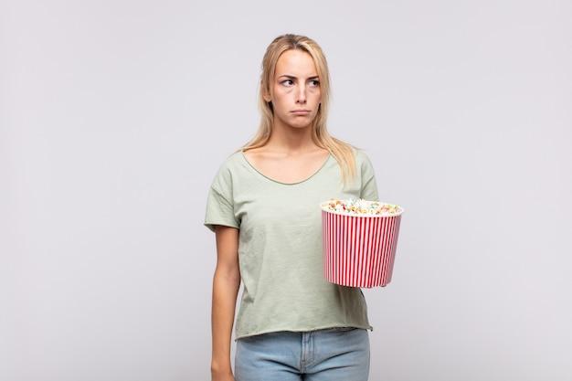 Jeune femme avec un seau de pop corns se sentant triste, bouleversée ou en colère et regardant sur le côté avec une attitude négative, fronçant les sourcils en désaccord