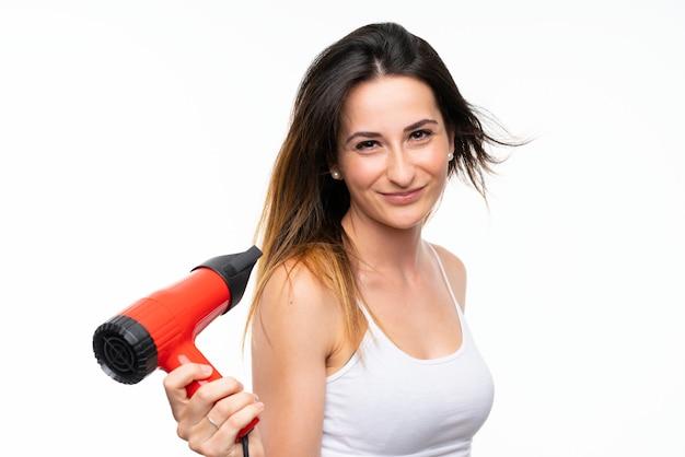 Jeune femme avec sèche-cheveux sur mur isolé