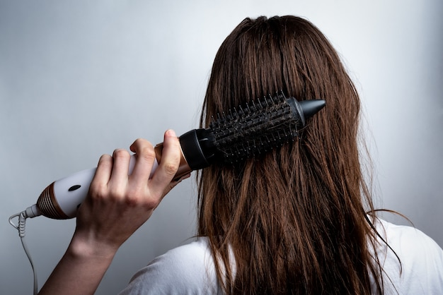 Jeune femme avec un sèche-cheveux et un peigne se brosser les cheveux.