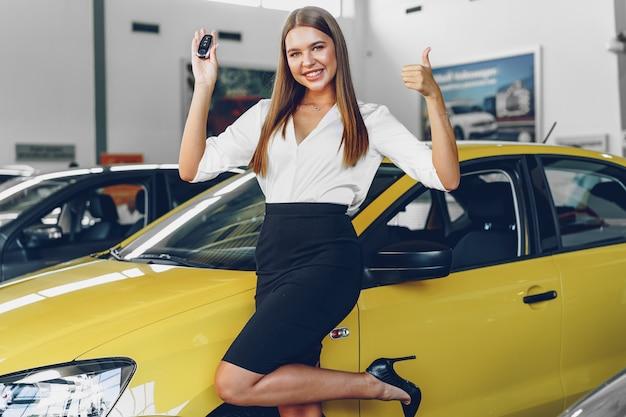 Jeune femme séduisante, acheter une nouvelle voiture dans un salon de voiture