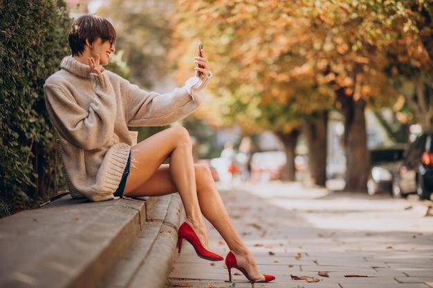 Jeune femme séduisante à l'aide de téléphone